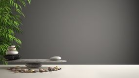 Empty interior design feng shui concept zen idea, white table or shelf with pebble balance and green bamboo, over dark gray backgr. Ound copy space stock photo