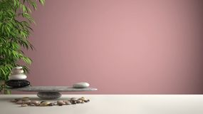 Empty interior design feng shui concept zen idea, white table or shelf with pebble balance and green bamboo, over pink background. Copy space stock image