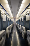 Empty interior of a passenger train car aka coach or carriage . Rows of unoccupied seats and folding tables in economy Stock Image