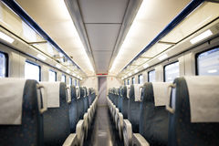 Empty interior of a passenger train car aka coach or carriage . Rows of unoccupied seats and folding tables in economy. Or second class. Public transport Royalty Free Stock Image