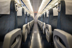 Empty interior of a passenger train car aka coach or carriage . Rows of unoccupied seats and folding tables in economy. Or second class. Public transport Stock Photography