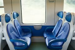 Empty interior of the train for long and short distance in Europe, Italy, train carriage with blue seats stock photos