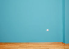 Empty interior with wooden floor, plug in wall and blue wall Stock Photos