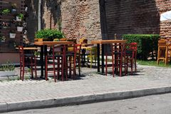 Empty, Inviting Chairs and Tables. Empty tables and chairs in Albanian sidewalk cafè.  Flower arrangements in buckets on the wall. Brick wall in the background Stock Images