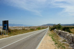 Empty Island Road with Mountains in Distance. Empty Island Road with Travel Sign and Mountains in Distance Stock Photography