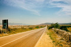 Empty Island Road with Mountains in Distance Royalty Free Stock Photography