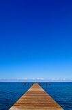 Empty jetty. An empty jetty facing out on a dark blue sea underneath a clear blue sky Stock Image