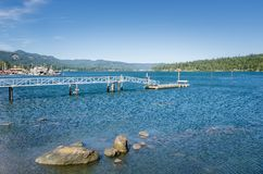 Empty Jetty in a Harbour and Blue Sky. Deserted Jetty in a Harbour with Rocks in Foreground and Forested Mountains in Background on a Sunny Summer Day. Sooke, Bc royalty free stock photography