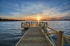 Empty jetty on lake. View of wooden jetty on beautiful lake just before sunset, Mazury, Poland Royalty Free Stock Photos