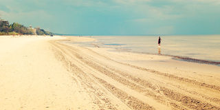 Empty Jurmala beach with lonely girl figure - retro filter. Spring seascape with lonely girl figure - retro filter. Sandy dunes and Baltic sea - vintage effect stock photo