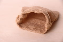 Empty jute sack on wood background Stock Photos