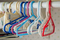 Empty Kids Clothing Hangers. Children's clothing hangers with no closthes hanging on a bar in a laundry room waiting to be filled Stock Photo
