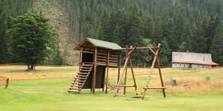 Empty kids playground. In mountains with house and tree behind Royalty Free Stock Images