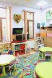 Empty kindergarten classroom. Clasroom in kindergarten with decoration and objects for preschool children Stock Photos