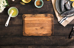Empty kitchen board on wooden table with fresh raw fish. With lemon and spices for cooking healthy food , top view. Healthy food and diet concept Stock Photos