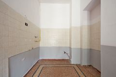 Empty kitchen interior with tiled floor before restoration. Empty kitchen interior with tiled floor and part of the wall in Europe Stock Images