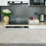Kitchen table top. Empty kitchen stone table top with modern kitchen in background stock image