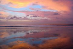 Empty Kuta beach with amazing colors sunset and sky reflection, Bali, Indonesia Stock Photos