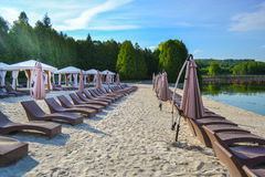 Empty lake beach with lounges. Morning sun is shinening on wet sand Royalty Free Stock Photos