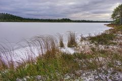 Empty lake with ice cover in winter day royalty free stock photography