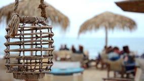 Empty lamp in a beach bar or cafe is swinging on a sea breeze on a Black sea seaside. Blurred sea. HD. 1920x1080 stock footage
