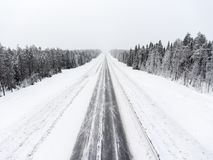 Empty lane of northern asphalt highway at winter blizzard. Northern Karelia, Russia. Empty lane of northern asphalt highway at winter blizzard. Northern Karelia Royalty Free Stock Photography