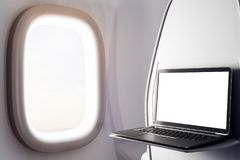 Empty laptop in airplane. Close up of laptop with empty screen next to airplane window. Freelance concept. Mock up, 3D Rendering Royalty Free Stock Photo