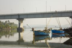 Empty large fishing boats and a bridge over the river and its reflection in the water against the green trees on the shore. A empty large fishing boats and a stock images
