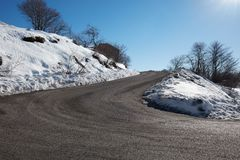 Empty, large mountain road with snow on sides, clear blue sky. In a sunny winter Royalty Free Stock Photos