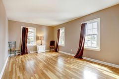 Empty large room with three windows and hardwood. Stock Photo