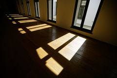 Empty large room. Window frames cast shadows on the floor of a wide empty room Royalty Free Stock Photo