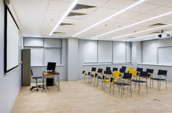 Empty lecture hall. With black and yellow chairs and TV projector Royalty Free Stock Photos