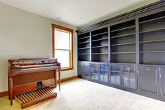 Empty library office room with piano. New luxury home interior. Black shelves royalty free stock photos