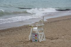 Empty Lifeguard Chair - Beach is Closed. An empty lifeguard chair on a Lake Michigan beach. An early summer storm churns up waves along the typically calm shore royalty free stock image