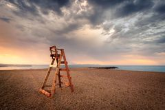 Empty lifeguard chair on the beach early in the day stock images
