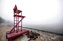 Empty lifeguard chair on the beach on a foggy morning. Stock Photos