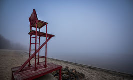 Empty lifeguard chair on the beach on a foggy morning. stock photography