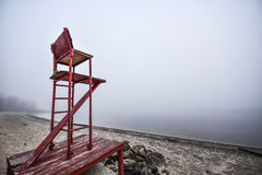Empty lifeguard chair on the beach on a foggy morning. stock image
