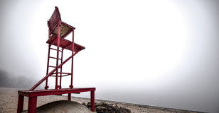 Empty lifeguard chair on the beach on a foggy morning. Royalty Free Stock Photography