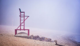 Empty lifeguard chair on the beach on a foggy morning. royalty free stock photos