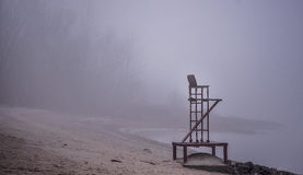 Empty lifeguard chair on the beach on a foggy morning. Stock Images