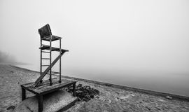 Empty lifeguard chair on the beach on a foggy morning. A lonely lifeguard seat stands empty in the fog on a November beach in Ontario Canada. Black and white royalty free stock photos