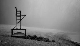Empty lifeguard chair on the beach on a foggy morning. Stock Photo