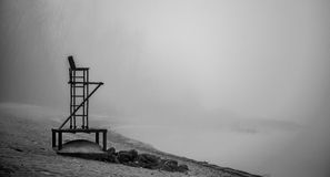 Empty lifeguard chair on the beach on a foggy morning. Royalty Free Stock Images