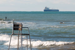 Empty lifeguard chair, surfers in sea and cargo ship in backgrou Royalty Free Stock Images