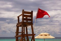Empty Lifeguard Chair and Umbrella at Beach. Abandoned lifeguard chair at a Caribbean beach, with the horizon over the ocean in the background and a red flag royalty free stock photography