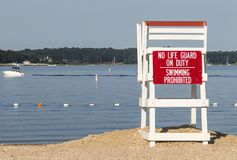 Empty lifeguard stand looking over the calm bay with a boat in the background. An empty lifeguard stand with a sign that saying no life guard on duty swimming is royalty free stock photography