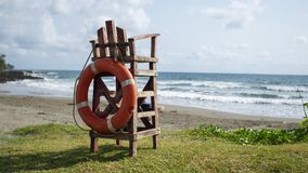 Empty lifeguard wooden watch chair. Lifeguard empty watch chair on a hot summer beach. Safety concept royalty free stock images
