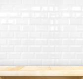 Empty light wood table and white ceramic tile brick wall in back.  Royalty Free Stock Photo