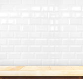 Empty light wood table and white ceramic tile brick wall in back Royalty Free Stock Photography